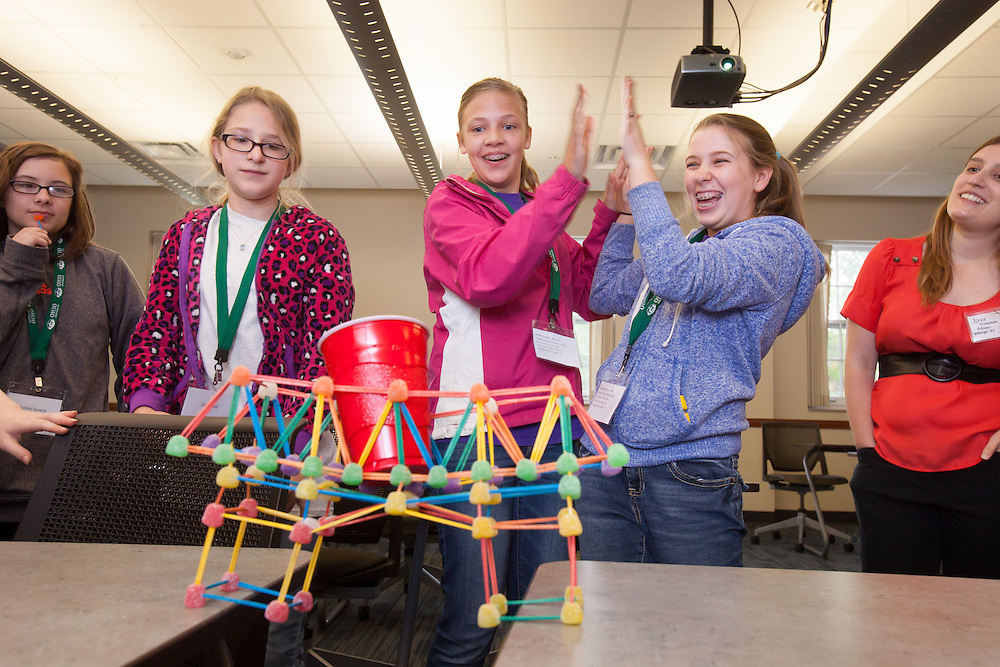 Jordan Mader, left and Meredith Coil celebrate while their gumdrop bridge withstands the weight test during the Tech Savvy workshop at Ohio University May 17, 2014. The event exposes girls from sixth through ninth grade to the field of science, technology, engineering and math.   Photo by Ohio University / Jonathan Adams