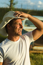 Profile of a laughing cowboy holding his cowboy hat