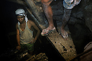 Miners working in the dangerous and cramped tunnels with no regard for health and safety in the rush for gold. Mount Diwata, Mindanao, The Philippines.