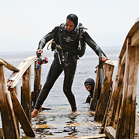 "A diver makes his way along a wooden bridge after diving in the Blue Hole outside of Dahab, Egypt. The Blue Hole is notorious for the number of diving fatalities which have occurred there, earning it the sobriquet ""World's Most Dangerous Dive Site"" and the nickname ""Diver's Cemetery"". The site is signposted by a sign that says ""Blue hole: Easy entry"". Accidents are frequently caused when divers attempt to find the tunnel through the reef (known as ""The Arch"") connecting the Blue Hole and open water at about 52 m depth. According to dive experts roughly 10 people die each year. April 2012."