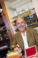 Portrait of cheerful mature man smoking cigar in tobacco store