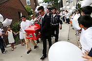 Imanol Arellano, 13 (left), and Brayan Macias, 18, help carry out the casket as loved one line the sidewalk with balloons to release in Irving Aguilar Gonzalez's honor Thursday, June 4, 2015, following a funeral Mass for the 6-year-old boy at Basilica of St. John in Des Moines. Irving was killed when a pickup truck crashed through the backyard of his home as Irving was jumping on his trampoline.