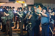 "Police and protesters clash in the streets of Ferguson. Heavily armed police provoked many of the protesters as they swooped in, guns pointing, to  arrest deemed ""troublemakers"" among the protesters in downtown Ferguson following the killing of unarmed Michael Brown (18)."