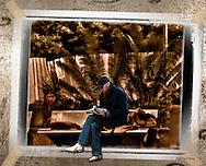 Homeless reading on park bench in Herzliya Israel