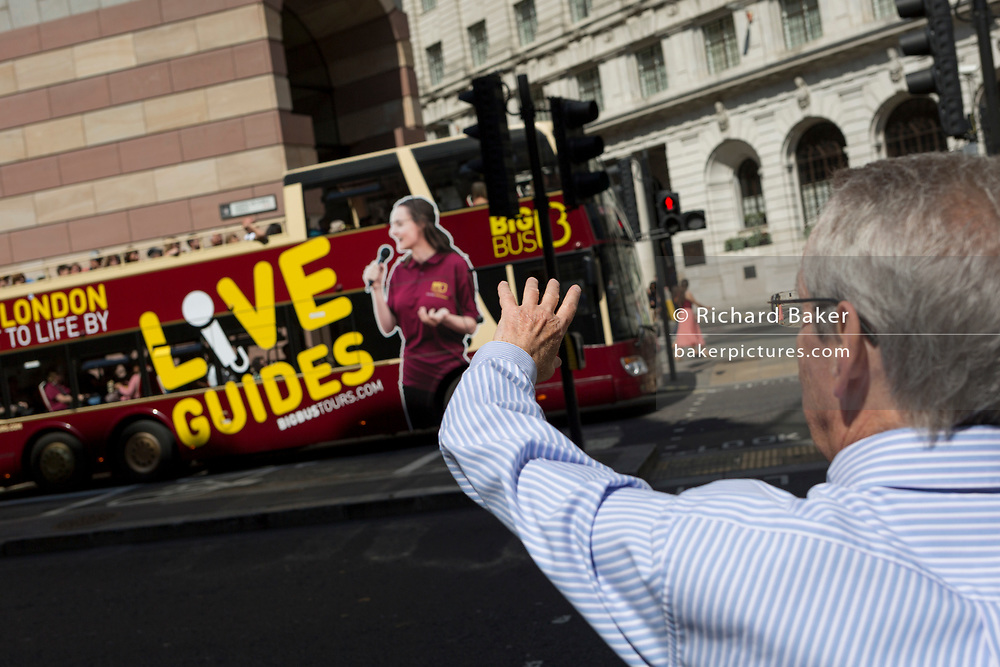 A man waves at a passing tour bus driving along Queen Victoria Street in the City of London, the capital's financial district (aka the Square Mile), on 22nd August 2019, in London, England.