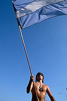 April 1986, Buenos Aires, Argentina --- A shirtless young man waves an Argentine flag at a workers' Peronist  rally in Buenos Aires, Argentina. --- Image by © Owen Franken/CORBIS