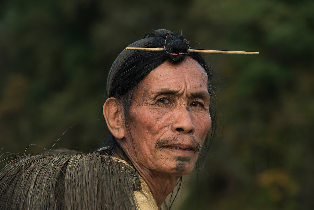 Apatani man showing hair knot. Skewer or Piidin Khotu is used to impale the hair knot. Lecha or haversack with fur like fibres used as rain shield, Byopa or cane wicker headgear has hornbill beak.<br /> Apatani Tribe<br /> Ziro Valley, Lower Subansiri District, Arunachal Pradesh<br /> North East India