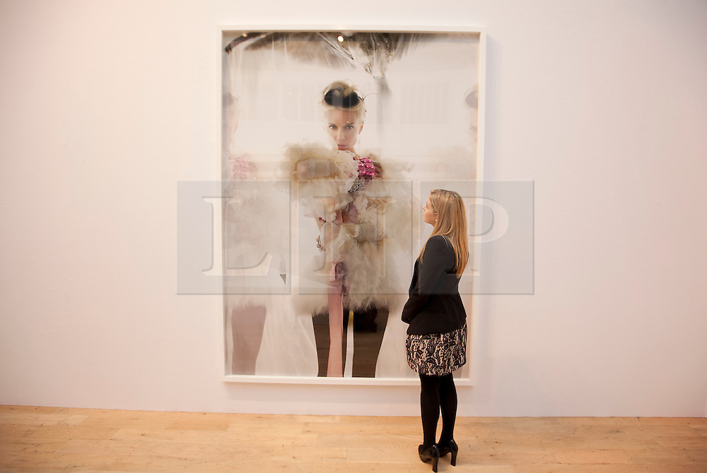 © Licensed to London News Pictures. 21/06/2012. LONDON, UK. A member of Christies' staff looks at a picture of fashion muse Daphne Guinness taken by Mario Testino (Est: £20,000-30,000) at Christies South Kensington Auction House in London today (21/0612) ahead of a charity auction.  The auction, held in aid of The Isabella Blow Foundation, features 102 lots of shoes, clothes and photographs from Daphne Guinness's private collection and is expected to realise in the region of £100,000 when it takes place on the evening of the 27th of June. Photo credit: Matt Cetti-Roberts/LNP