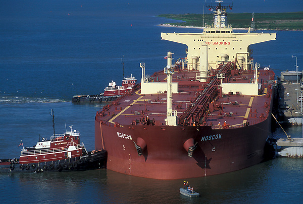 Docked tanker being held by tugboats in the Port of Houston