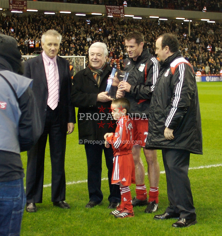 LIVERPOOL, ENGLAND - Tuesday, January 15, 2008: Liverpool's Jamie Carragher with his son receive an award on the pitch with Chief-Executive Rick Parry, Ian Callaghan (who holds the record number of appearances for Liverpool 857) and manager Rafael Benitez before he makes his 500th career appearance for the Reds during the FA Cup 3rd Round Replay agaisnt Luton Town at Anfield. (Photo by David Rawcliffe/Propaganda)