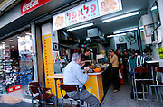 Israel Tel Aviv Local people eating at a Falafel stand in Sheinkin street near the entrance to the Carmel Market