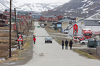 Visitors stroll down a street in Longyearbyen, a small Norwegian community situated at 78.22N 15.65E the worlds most northern community of any kind with greater than 1000 permanent residents.  Spitsbergen Island, Svalbard, Norway.