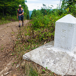 A man hikes on the border swath between Easton, Maine and Bath, New Brunswick. Part of the International Appalachian Trail.
