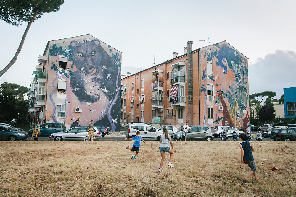 ROME, ITALY - 27 JUNE 2017: Children play in Parco Giulietto, a  park where the &quot;Don Giovanni OperaCamion&quot; - an open-air opera performed on a truck - will take place, in San Basilio, a suburb in Rome, Italy, on June 27th 2017.<br /> <br /> Director Fabio Cherstich&rsquo;s idae of an &ldquo;opera truck&rdquo; was conceived as a way of bringing the musical theatre to a new, mixed, non elitist public, and have it perceived as a moment of cultural sharing, intelligent entertainment and no longer as an inaccessible and costly event. The truck becomes a stage that goes from square to square with its orchestra and its company of singers in Rome. <br /> <br /> &ldquo;Don Giovanni Opera Camion&rdquo;, after &ldquo;Don Giovanni&rdquo; by Wolfgang Amadeus Mozart is a new production by the Teatro dell&rsquo;Opera di Roma, conceived and directed by Fabio Cherstich. Set, videos and costumes by Gianluigi Toccafondo. The Youth Orchestra of the Teatro dell&rsquo;Opera di Roma is conducted by Carlo Donadio.