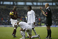 Photo: Aidan Ellis.<br /> Bolton Wanderers v Arsenal. The Barclays Premiership.<br /> 03/12/2005.<br /> Arsenal's Lauren is cautioned by the referee after a foul on Bolton's Stelios