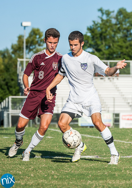 Cox Mill's Trey Holland and Jay M. Robinson's Ryan Bogart fight for the ball Monday afternoon at Cox Mill High School.