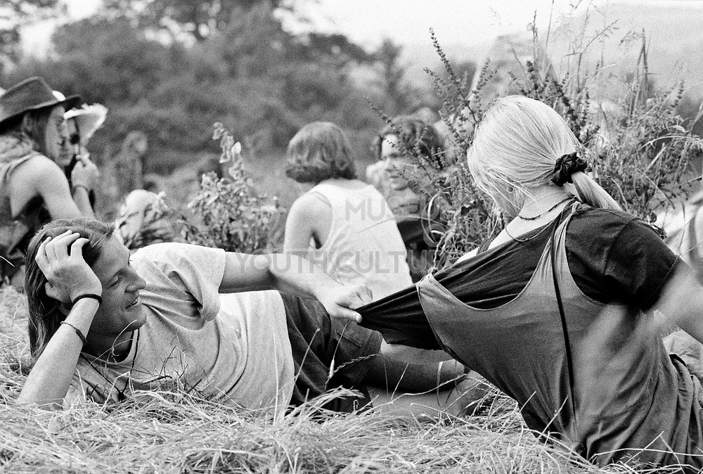 Young white male pulls t-shirt of young white female,  they are sat in a field in front of a group of people. Glastonbury 1992