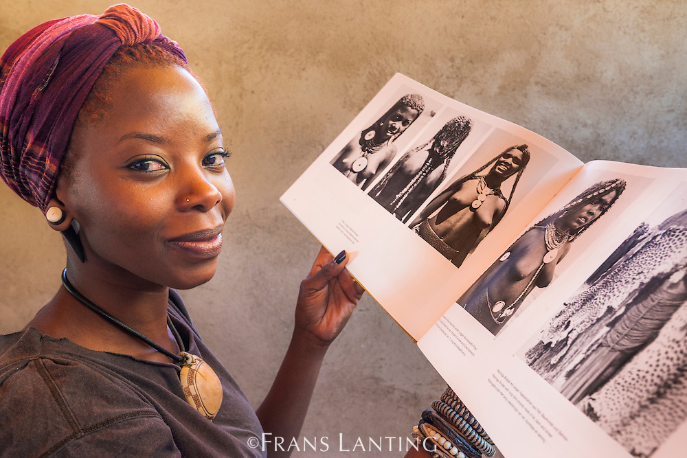 Woman in modern attire with historical photos of tribal women from Ovamboland, Namibia