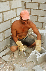 Builder constructing breeze block wall at Gibara; Cuba,