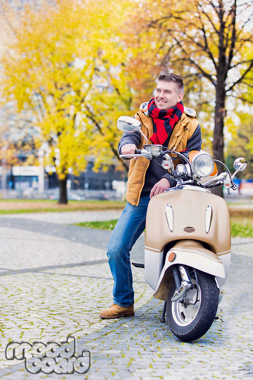 Portrait of mature attractive man sitting on motor bike while waiting in park