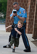 Six-year old Grant Bierce of Columbia really isn't running from the law.   Lt. Paul Yodzis of the Howard County Police Department is in the process of clocking the young speedster as he races up the sidewalk in front of Guildford Elementary School in Oakland Mills.  It's all part of a wellness fair the school hosted Friday. and for Grant, he's doing pretty well at 10 m.p.h.