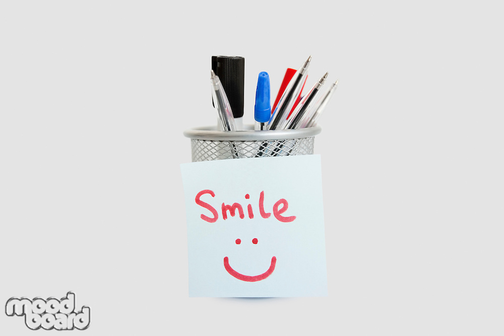 Close-up of adhesive notepaper with smiley face stuck on pen holder over white background