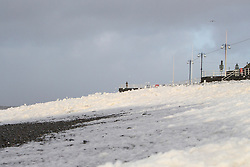 © Licensed to London News Pictures. 27/12/2013. Aberystwyth, UK Sea foam lies like snow on the beach at Aberystwyth during high winds.. Photo credit : Jon Freeman/LNP