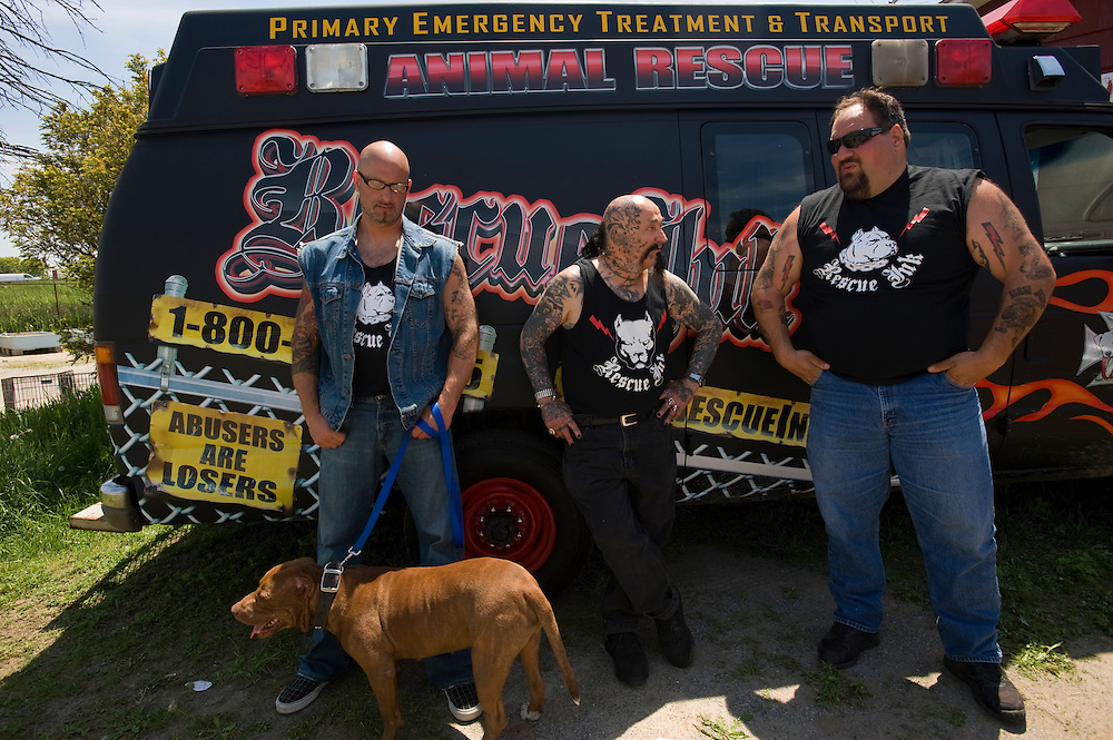 "Rescue Ink, Long Island, New York, taettowierte Motoradgang, Verein zur Rettung mishandelter Hunde und anderer Tierarten.vlnr:.Jonny ""O"", ""Batzo"", ""Big Ant"" vor dem Tierkrankenwagen.Hund: Rebel.Rescue Ink rettete dem Pitbull 'Rebel' das Leben, er war in Virginia als Koeder fuer Kampfhunde eingesetzt worden und erlitt schwerste Verletzungen. ..Rescue Ink, the animal rescue group that brings an in your face approach to the fight against animal abuse and neglect. The goups members are heavily tattooed and ride motorbikes. Their pitbull 'Rebel', who lives at their headquarters, was rescued from a dog fighting operation, where he was used as bait. He was near death when two members of Rescue Ink flew to Virginia to save him..Foto © Stefan Falke."