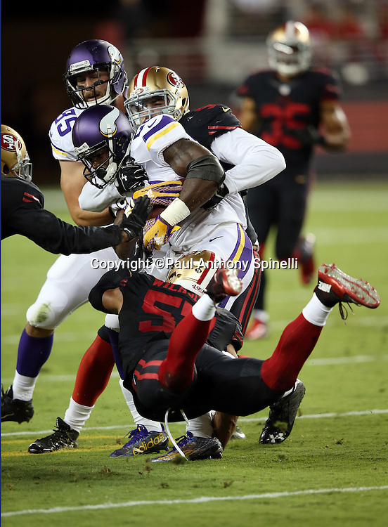 Minnesota Vikings running back Adrian Peterson (28) gets gang tackled by diving San Francisco 49ers inside linebacker Michael Wilhoite (57) and a teammate after catching a pass in the flat and runs for a gain of 17 yards and a second quarter first down during the 2015 NFL week 1 regular season football game against the San Francisco 49ers on Monday, Sept. 14, 2015 in Santa Clara, Calif. The 49ers won the game 20-3. (©Paul Anthony Spinelli)