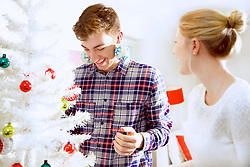 Smiling Couple Decorating Christmas Tree
