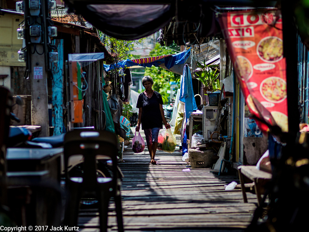 "21 JUNE 2017 - BANGKOK, THAILAND: A woman walks home with her groceries in a community along the Chao Phraya River south of Krung Thon Bridge. This is one of the first parts of the riverbank that is scheduled to be redeveloped. The communities along the river don't know what's going to happen when the redevelopment starts. The Chao Phraya promenade is development project of parks, walkways and recreational areas on the Chao Phraya River between Pin Klao and Phra Nang Klao Bridges. The 14 kilometer long promenade will cost approximately 14 billion Baht (407 million US Dollars). The project involves the forced eviction of more than 200 communities of people who live along the river, a dozen riverfront  temples, several schools, and privately-owned piers on both sides of the Chao Phraya River. Construction is scheduled on the project is scheduled to start in early 2016. There has been very little public input on the planned redevelopment. The Thai government is also cracking down on homes built over the river, such homes are said to be in violation of the ""Navigation in Thai Waters Act."" Owners face fines and the possibility that their homes will be torn down.          PHOTO BY JACK KURTZ"
