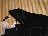 Teacher with student sitting at piano in music class