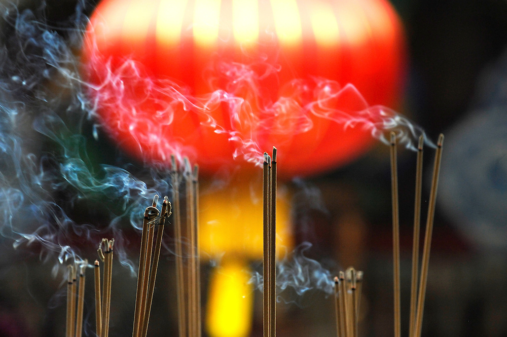 Incense sticks buring in side a temple in Malaysia with red lantern in background<br /> .