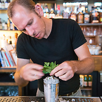 A bartender arranges mint sprigs on a cocktail at Sovereign Remedies, a bar and eatery located at 29 N Market Street in downtown Asheville, North Carolina.