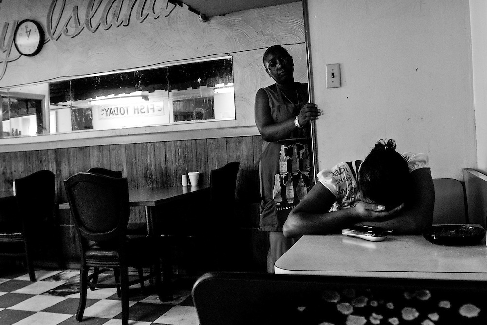 Arnita Rudder, left, looks at her daughter Latoya, after Latoya recently learned a friend of her son's was gunned down in Gary, Indiana. Rudder has since closed her restaurant and moved away from Gary. The city's population peaked in the early 1960s at roughly 174,000 residents but has fallen to around 80,000 according to the latest U.S. Census in 2010. In addition to the collapsing infrastructure and deteriorating buildings, the number of abandoned houses is sharply increasing as people leave the city. (© William B. Plowman/Redux)