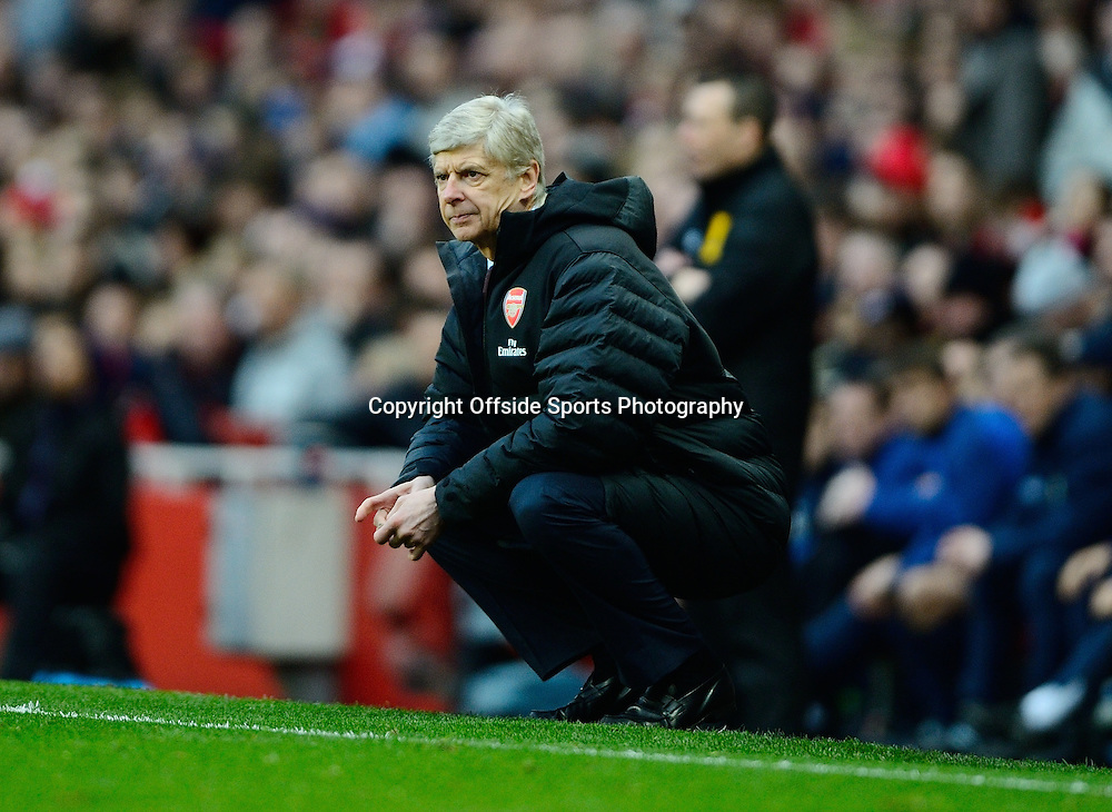 16 February 2013 - FA Cup 5th Round - Arsenal v Blackburn Rovers - A dejected  Arsene Wenger, Manager of Arsenal crouches on the touchline - Photo: Marc Atkins / Offside.