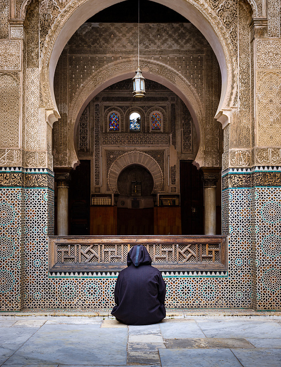 FEZ, MOROCCO - CIRCA MAY 2018:  Moroccan man seating at the courtyard of the Al-Attarine Madrasa in Fez. The courtyard of this small Marinid madrasa is a dazzling example of intricate Islamic architecture.
