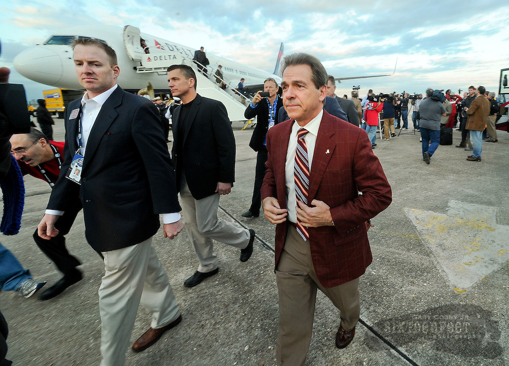 Daily Photo by Gary Cosby Jr.    ..The University of Alabama football arrives at the Louis Armstrong International Airport Wednesday afternoon as they begin the final preparations for the BCS Championship Game against conference rival LSU.  Coach Nick Saban leaves the plane on the way to an arrival news conference...................................