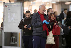 © Licensed to London News Pictures. 12/03/2020. London, UK. A commuter at Westminster Station, wearing disposable gloves. New cases of the COVID-19 strain of Coronavirus are being reported daily as the government outlines it's plans for controlling the outbreak. Photo credit: George Cracknell Wright/LNP