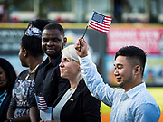 04 JULY 2019  - DES MOINES, IOWA: EHKLER TAW, right, originally from Myanmar, waves an American flag just he took the oath to become a naturalized American citizen. Thirty people became US citizens during a naturalization ceremony at the Iowa Cubs game in Des Moines. The naturalization ceremony is an Iowa Cubs 4th of July tradition. This is the 11th year they've held the ceremony.           PHOTO BY JACK KURTZ