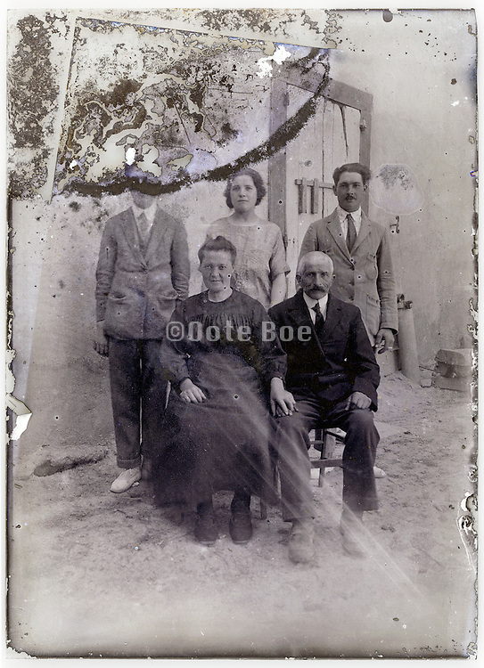 severely eroding and damaged glass plate with family portrait