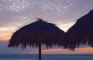Thatched beach umbrellas in silhouette at sunset<br /> Playa Ancon, Trinidad, Cuba