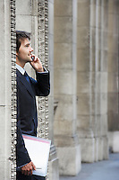 Businessman standing by colonnade pillars talking on cell phone