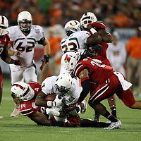 Louisville Cardinals defensive end Lorenzo Mauldin (94) tackles Miami Hurricanes running back Gus Edwards (7) during the NCAA Football Russell Athletic Bowl football game between the Louisville Cardinals and the Miami Hurricanes, at the Florida Citrus Bowl on Saturday, December 28, 2013 in Orlando, Florida. Louisville won the game by a score of 36-9. (AP Photo/Alex Menendez)