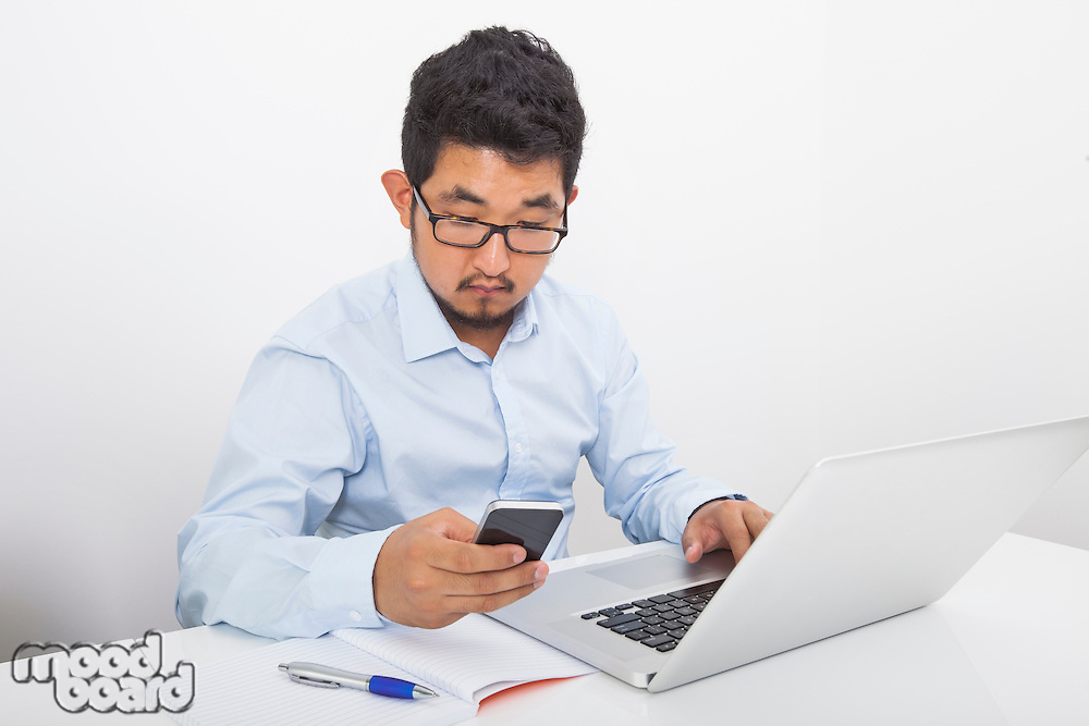 Young businessman using cell phone while working at desk in office