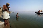 Hindu men pray and pay homage to the sacred River Ganges, Varanasi, India. January, 2004.