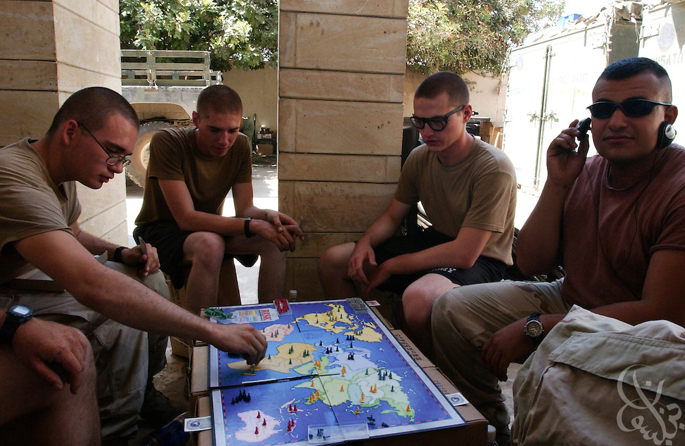 U.S. Army 101st Airborne soldiers play a game of RISK during down time at their base July 27, 2003 in Mosul, Iraq.