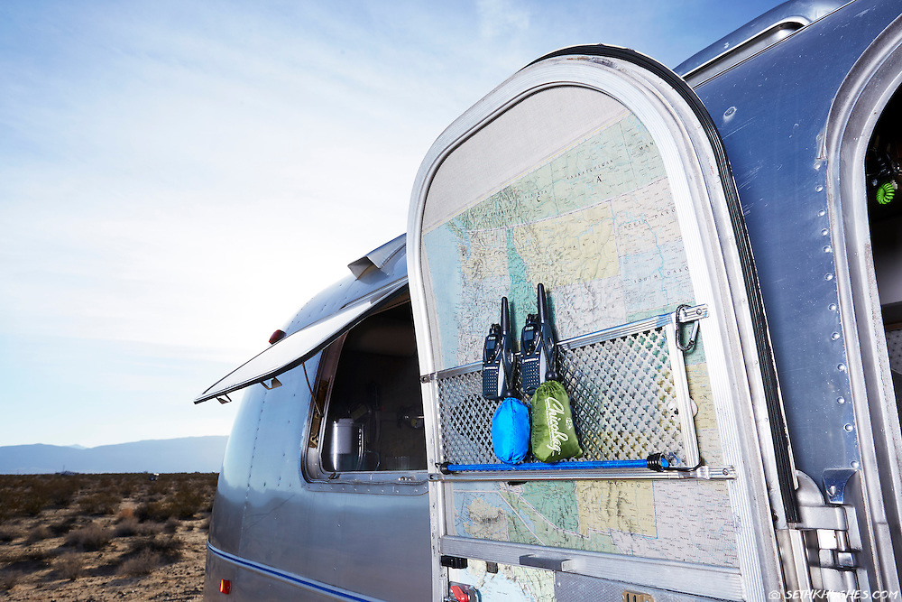 A map and 2-way radios affixed to an open Airstream door in the Anza Borrego desert of California.
