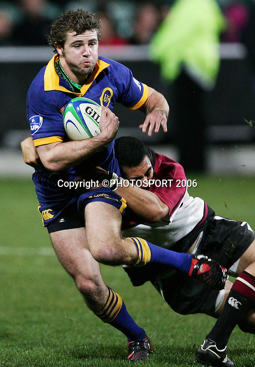 Otago first five Nick Evans is tackled during the Air New Zealand Cup pre season game between QBE Insurance North Harbour and Speight's Otago held at North Harbour Stadium in Auckland, New Zealand on Friday 14 July 2006. Photo: Tim Hales/PHOTOSPORT