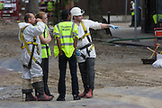Thames Water employees oversee the aftermath following a burst water main which closed the otherwise busy junction of Half Moon Lane and Dulwich Road in the south London area of Herne Hill. Emergency services were called at about 5am, when water inundated local businesses, forcing shopkeepers and owners to evacuate their properties and leave before electricity supplies were shut down. Copyright Richard Baker / Alamy Live News.